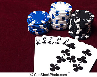 The assembled combination of flush in poker on red cloth with chips of different value.
