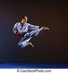 The athlete beats a kicking in a jump with red overlays on his hands