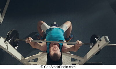 The athlete doing exercise with barbell on the exercise machine, top view