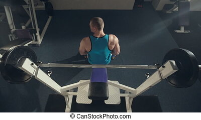 The athlete doing exercise with a barbell on the exercise machine,  top view