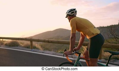 The athlete on a Bicycle goes from a rock on a mountain...