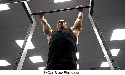 The athlete pulls on the bar at the gym