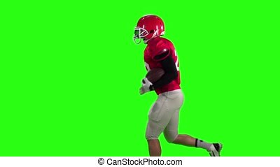 The athlete runs with the ball in his hands. Sow motion, green screen