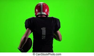 The athlete with the ball and helmet. Slow motion, green screen