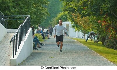 The athletic young man bodybuilder running past people in the park