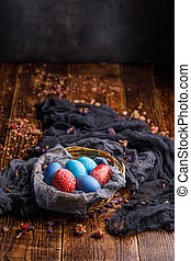 Basket with colored eggs in different colors on a wooden background.