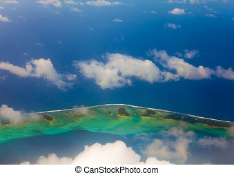 The atoll ring at ocean is visible through clouds. Aerial...