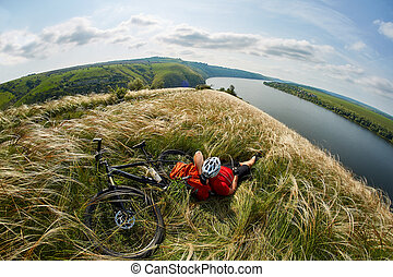 The attractive cyclist sitting on the grass on the meadow with mountain bike above river.