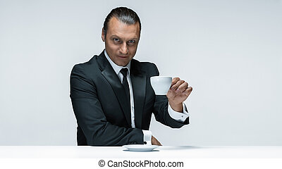 The attractive man in black suit on white background