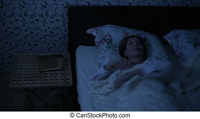 The average shot of a girl at night waking up gets out of bed. Low key. The effect of American night. Cold night light