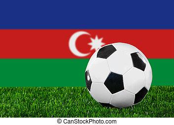 The Azerbaijani flag and soccer ball on the green grass.