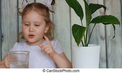 The baby girl and green plant. A child watering a flower and playing with it. Spathiphyllum.