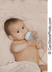 The baby holds a bottle for feeding lying on a blanket