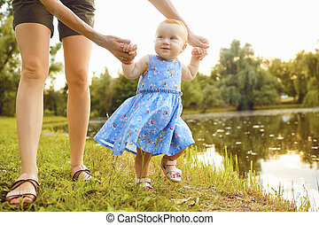 The baby with his mom takes the first steps in the park.