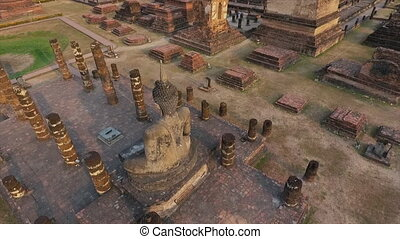A high angle shot of the back view of the statue of buddha meditating in an ancient wat in Sukhothai, Thailand