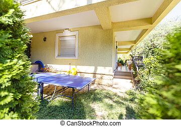 The back yard of a multi-storey residential building. The yard is fenced by a hedge of cypress trees. The courtyard has a veranda with wicker furniture. There is a tennis table on the grass