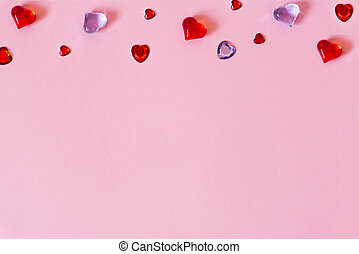 The background of Valentine's day. Border of beautiful different hearts on a pink background