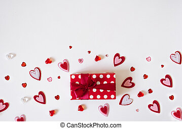 The background of Valentine's day. Red gift box with red satin ribbon and lots of different hearts