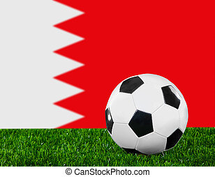 The Bahraini flag and soccer ball on the green grass.