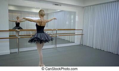 The ballerina in black tutu does par de bourree in front of the big mirror in the studio.