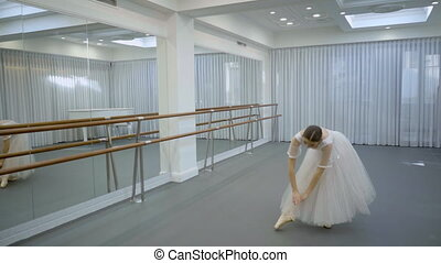 The ballerina in white long tutu repeating her variation in...