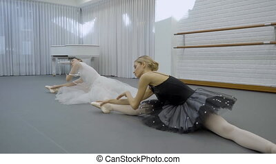 The ballerinas does the middle split and inclines to the...