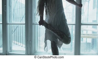 The ballerina's feet are on the windowsill. A ballerina on the window does stretching and gets on socks. Dance in white clothes.