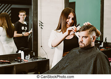 the barber cuts a bearded man with scissors in the salon