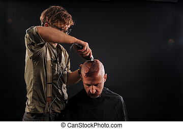 the barber shaves his head bald elderly man in the studio