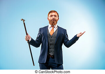 The barded man in a suit holding cane.