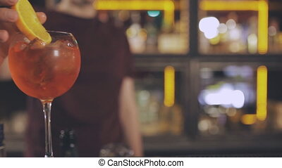 The barman at the bar counter puts an orange in a cocktail