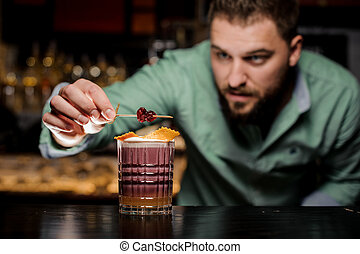 The barman decorates her cocktail. Work as a hobby.