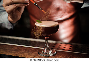 The barman decorates the cocktail with a gold powder