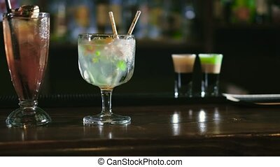 The barman is preparing a cocktail in the night club bar