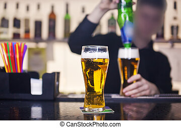 The barman pours a glass of beer in the pub