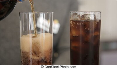 Pour cola and ice in the glass beaker closeup