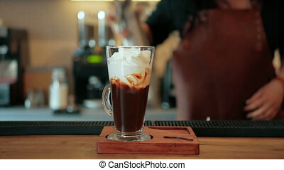The bartender makes a cocktail of liquor, coffee and whipped cream. step by step