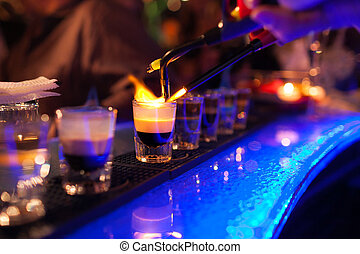 The bartender makes hot alcoholic cocktail and ignites bar. elite night club during party prepares a fiery cocktail. Fire on bar.