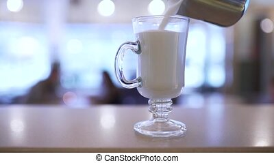 the bartender pours milk into a glass