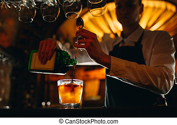The bartender prepares a cocktail at the bar. The bartender pours alcohol from a bottle.