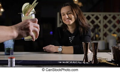 The bartender puts an exclusive cocktail for the attractive...