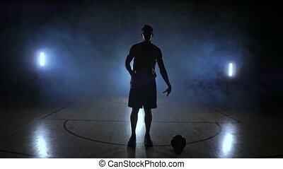 The basketball player goes to the camera and knocks the ball...