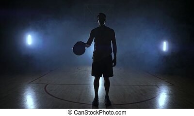 The basketball player stands on a dark Playground and holds the ball in his hands and looks into the camera in the dark with a backlit in slow motion and around smoke