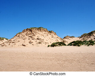 the beach at formby merseyside with tall sand dunes covered in rough grass and a blue summer sunlit sky