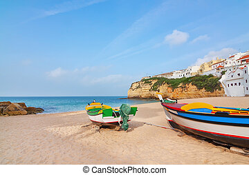 The beach at the village of Carvoeiro with fishing boats in the foreground. Portugal, summer.