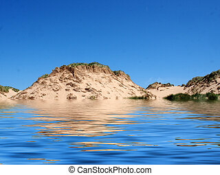 the beach from the sea at formby merseyside with tall sand dunes covered in rough grass and a blue summer sunlit sky