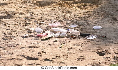 The beach is contaminated with plastic garbage. Garbage on the beach, dirty sand