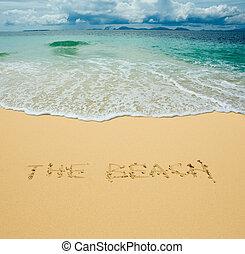the beach written in a sandy tropical beach