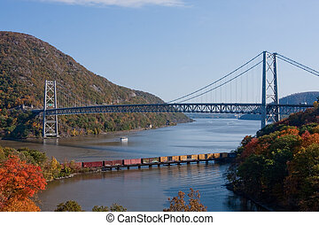The Bear Mountain Bridge and a freight train traveling down the Hudson River.