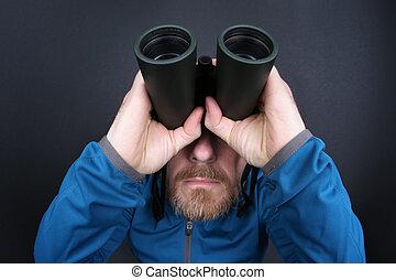 the bearded man looks up through binoculars on grey background